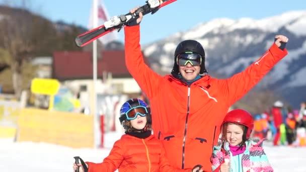 junger Vater und seine beiden Kinder im Urlaub in einem Skigebiet. Familienporträt in roten Skianzügen und Ausrüstung