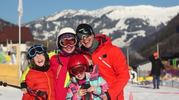 Eine große, freundliche Familie ruht im Winter in den Alpen. Mann, Frau und zwei Kinder in Skiausrüstung