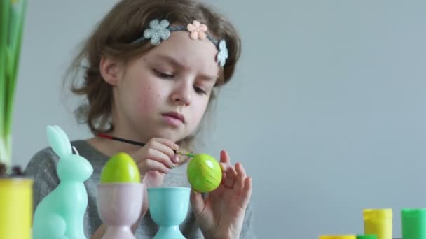 Portrait of a schoolgirl with a brush and paints decorating an Easter egg. Christian traditions, Easter concept