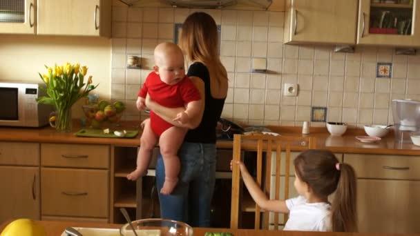 Mladá žena v domácnosti s dítětem v náručí živí předškolní dceru. Maminka s dvěma dětmi. Den matek