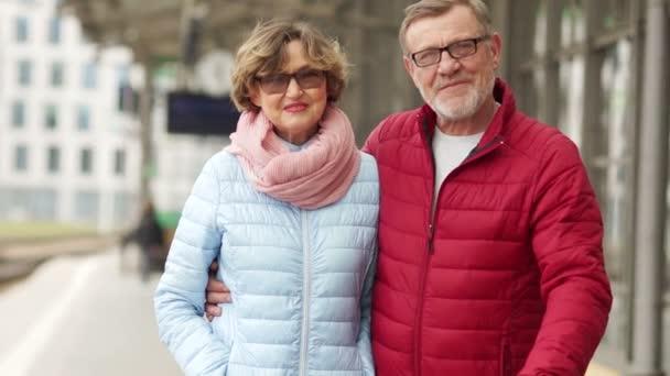 Manžel a manželka na jaře projít městem. Podívejte se na rám, objetí a smích. Datum starší pár. Obě jsou na sobě brýle oblečený v neformálním stylu