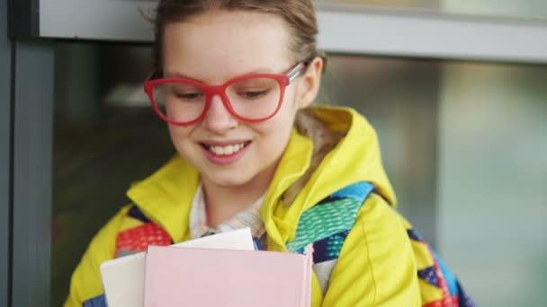 Közelről portré egy gyönyörű iskolás szemüveg könyveket a kezükben. Vissza az iskolába