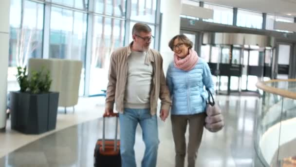 Husband and wife retired at the airport. They are landing and have fun talking. In anticipation of a pleasant trip