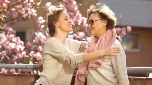 Adult daughter hugging her mother on the balcony against the backdrop of a blooming magnolia. Women are dressed in beige clothes, the wind develops hair, bright spring sun, mothers day