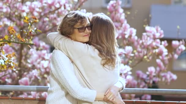 Mature mother hugging her adult daughter. Two women congratulate each other on the holiday, spring morning against a blossoming magnolia, feast of femininity, mother and daughter, mothers day