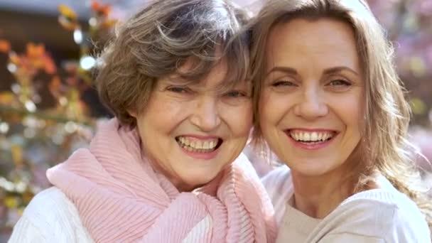 Dvě krásné ženy, starší a mladé, dívejte se do kamery a Smějte se. Blízký portrét, den matek, den mezinárodních žen