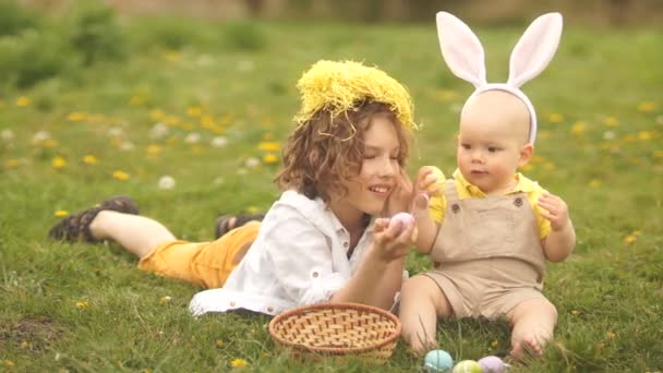 Two brothers, a teenager and a baby are resting in a park on a glade. Easter concept, bunny ears, easter basket and eggs. A dog runs past them