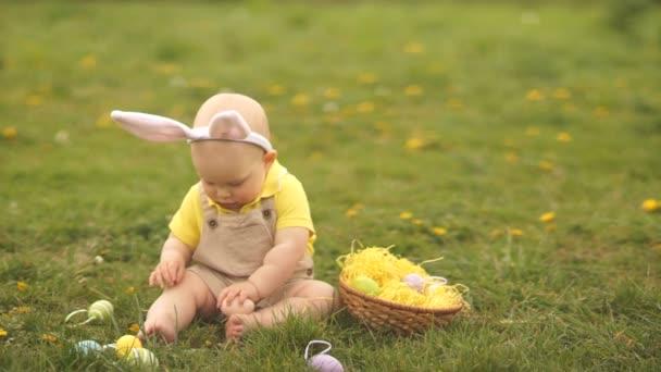 Milé dítě z velikonočního kostýmu shromažďuje velikonoční vajíčka v koši, který sedí v trávě v parku. Jarní piknik, šťastná velikonoční rodina