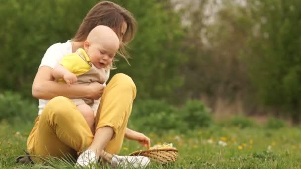 Rozhněvaný dítě v náručí matky. Dítě pláče, Máma uklidní. Žena a dítě na pikniku v parku