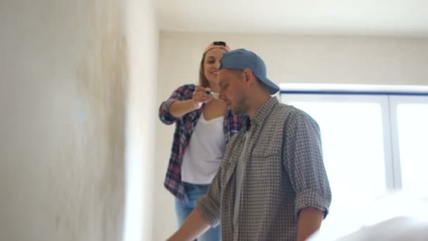 Home renovation, happy newlyweds hang painting and shelf on wall in new apartment. Real estate