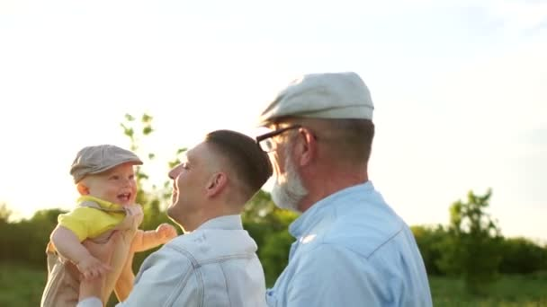 Nagyapja, fia és unokája sétálni. Apa veti fel egy egyéves kisbaba. Apák napja boldog családi hétvége