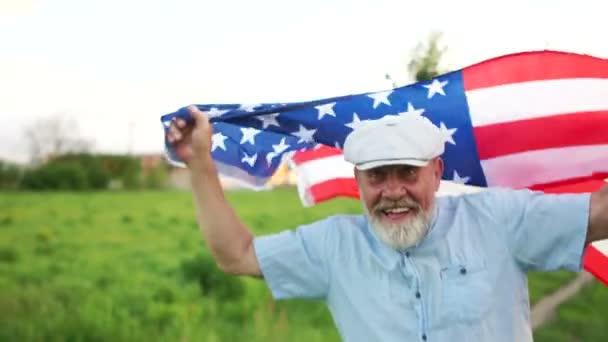 Hazafias nap. Egy idős férfi az amerikai zászló a háttérben a zöld fű. Amerikai függetlenségi nap ünnepe július 4.
