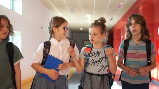 Classmates teenagers go down the hall to school for a lesson. School break, back to school. Girl joking pushes girlfriend, school conflict, teen bullying