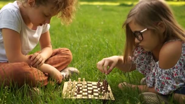 School holidays, intellectual games for teens. Two teen girlfriends playing chess in the park sitting on the grass
