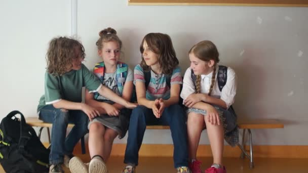 School friendship. Classmates console their friend while sitting on a bench in the school hallway, back to school