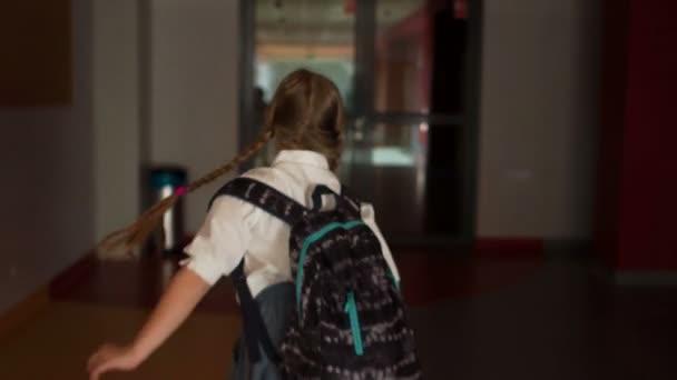 Dívka s brašny běží na hodině ve školní chodbě. Pohled zpět. Zpět do školy