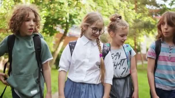 Vissza az iskolába. Gyerekek iskolába menni, és jó szórakozást beszél, göndör iskolás mutatja a smartphone az osztálytársaival, az iskolai barátság