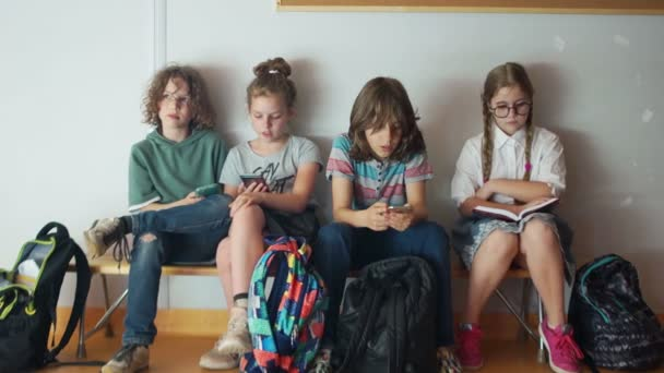 Teenageři během školní přestávky, každý pohled na telefony. Jedna dívka čte knihu, nudí se a je smutná