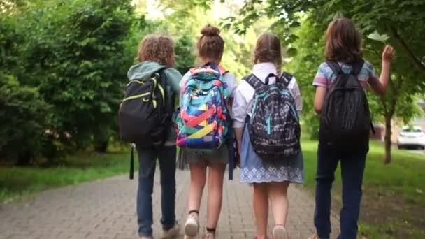 Klassenkameraden gehen auf der Allee zur Schule. Erster Schultag, zurück zur Schule. Kinder tragen Rucksäcke, Rückansicht