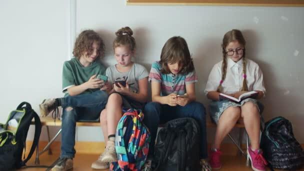 Zorničky a miniaplikace. Tři Teenageři jsou nadšení ze svých telefonů. Ctít studentka čte knihu, zatímco sedí vedle nich