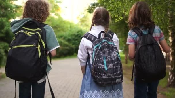 Iskolai barátság. Két fiú escort a lány az iskolából, az iskolai szeretet, vissza az iskolába, a hátsó kilátás
