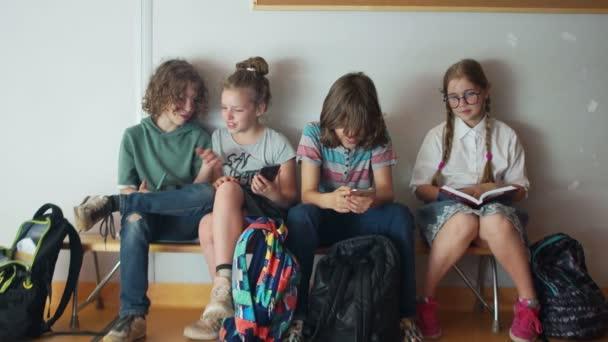 Tři Teenageři jsou nadšení ze svých telefonů. Nejlepší student si přečte knihu, která sedí vedle nich. Zorničky a miniaplikace. Internetová závislost, sociální síť