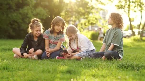 Iskolás fiúk és lányok aktatáskák ülni a fűben. A gyermekek elfoglalt tanul és megvitatása a smartphone. Gyerekek és gadgetek, vissza az iskolába