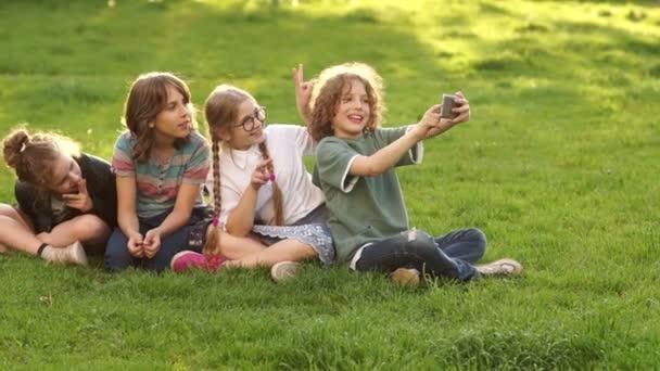 Mitschüler machen Selfie im Park. Vier Schulkinder, Teenager werden mit dem Smartphone fotografiert. Schulfreundschaft, frohe Schulferien