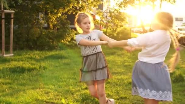 Dvě dívky pobíhnou kolem a otáčejí se na trávě v parku, v lese. Šťastné děti, školní svátky, paprsky západu slunce