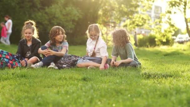 Čtyři žáci během školní přestávky, sedí na Mýtě v parku. Děti házou trávu. Zpět do školy