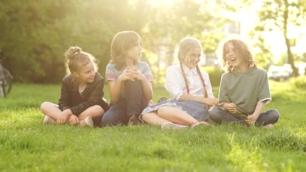 Beautiful schoolchildren, boys and girls laugh sitting on the grass during a school break. Back to school, a group of teenagers on a picnic. Sunset sun rays