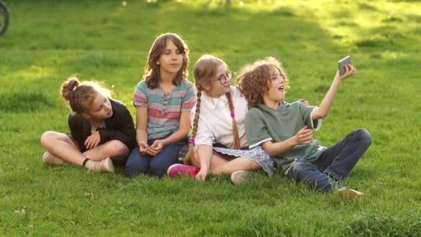 Děti ze školy sedí na trávě během školního přestávky. Spolužáci mají v parku selu.