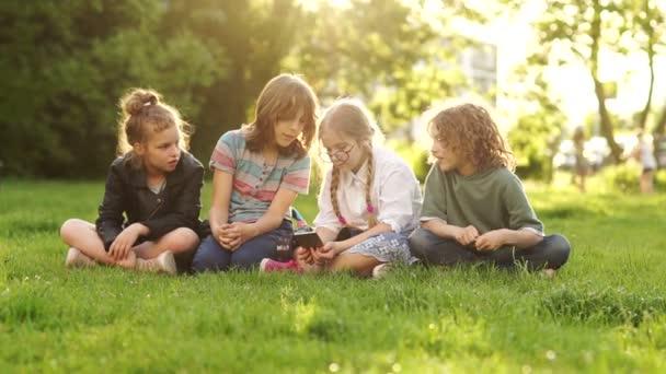 Skupina teenagerů sedícího na trávě během školní přestávky. Čtyři děti, chlapci a děvčata, sledujte a prodiskutujte smartphone v rukou jednoho z nich. Děti a miniaplikace zpět do školy