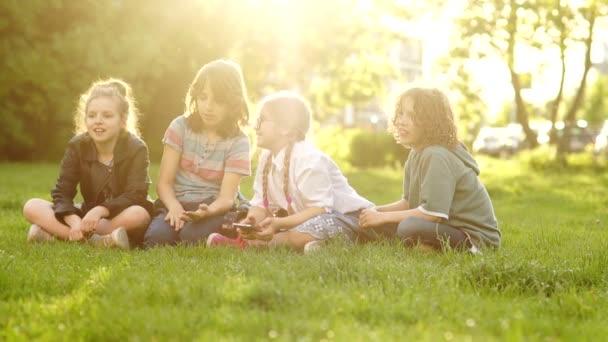 Šťastný žák během školní přestávky, sedí na Mýtě v parku. Děti házou trávu. Zpět do školy