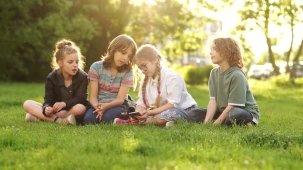 Four children, boys and girls watch and discuss the smartphone in the hands of one of them. Kids and Gadgets Back to School