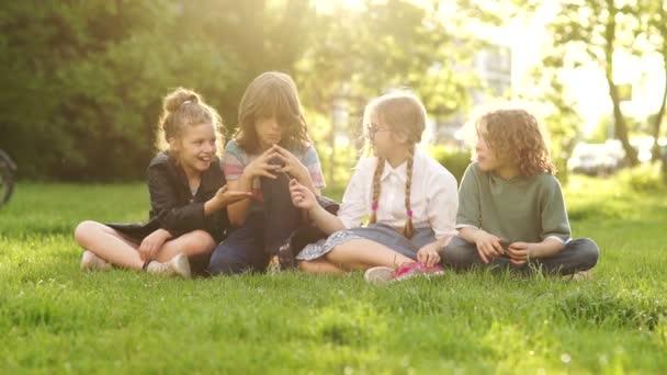 Zpátky do školy, studenti po škole. Veselí a přátelští spolužáci, kteří seděli v parku na trávníku během školního přestávky