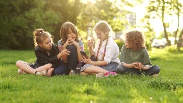 Kinder und Gadgets. Klassenkameraden reichen sich ein Smartphone, während sie auf dem Rasen im Park sitzen. Sonnenuntergang