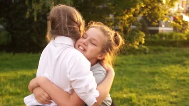 Dívky se smějí obejmout a smát se na pozadí slunečního světla, šťastného dětství, školních prázdnin, venkovního portrétu