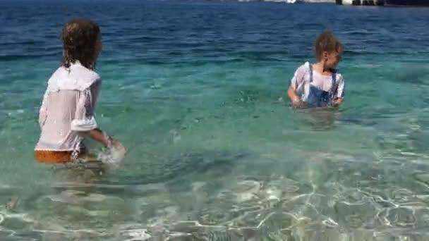 Junge und Mädchen planschen Wasser und stehen bis zur Taille im Meer. Kinderkleidung wird nass, glückliche Kindheit