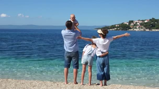 Happy family on the coast of the purest turquoise sea. Parents and their two children. Father throws baby up