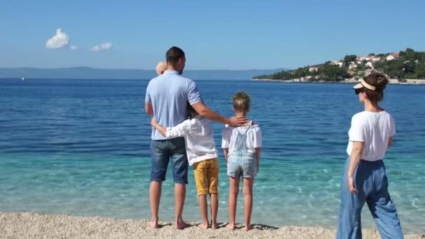 Šťastná rodina odpočívá na moři se třemi dětmi. Rodiče a děti stojí na břehu Jaderského moře, pohled zezadu