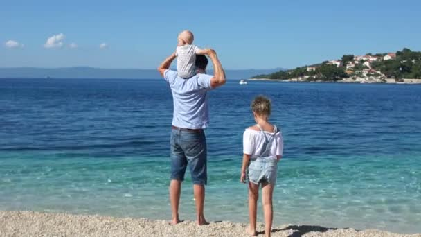 Big family with a toddler standing on the shores of the azure pure sea. Parents of ti three children travel