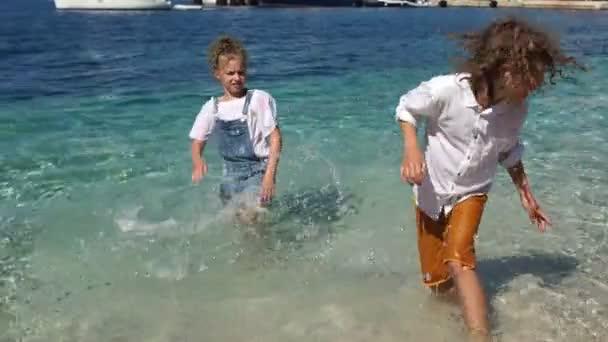 Šťastné děti se Radou a hrají v mořské vodě. Děti jsou mokré a šťastné, svátky s dětmi, školní prázdniny