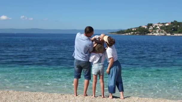 Family holidays on the Mediterranean coast. Friendly family with two children are standing on the seashore, kissing and hugging, rear view