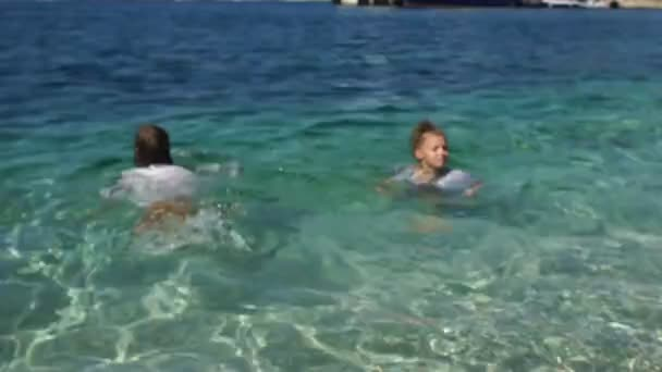 Děti plavou v tyrkysové mořské vodě přímo do šatů. Šťastné svátky s dětmi. Koncepce cestování