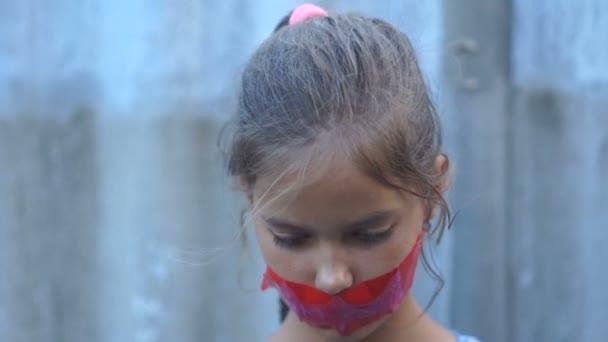 Portrét smutné mladé dívky. Mrazená ústa jsou utěsněné červenou sádrou. Domácí násilí, ochrana práv na dítě, spravedlnost mladistvých