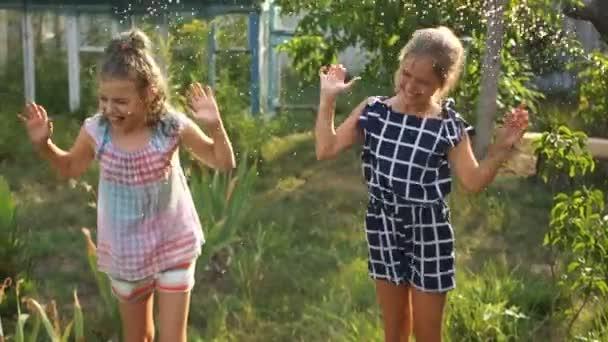 fröhliche Kinder, die sich an einem sonnigen Sommertag in einem Dorf im Garten vergnügen und unter den Wasserstrahlen aus einem Schlauch springen. Gartenbewässerung