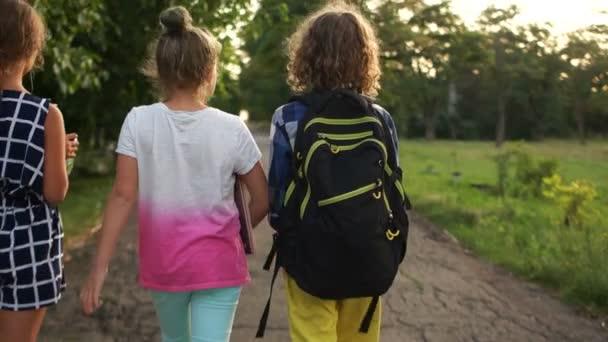 Három gyermek tért vissza az iskolából az esti, hátulnézet. Vissza az iskolába, faluiskola