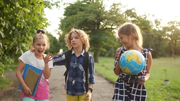 Happy children returning from school. Classmates are holding a large globe, sunset