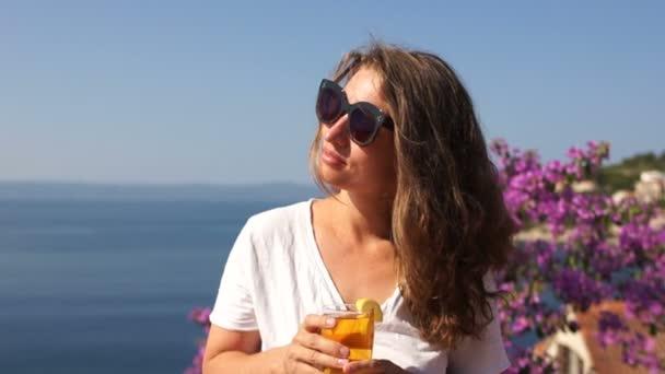 Retrato De Una Hermosa Chica En La Costa Del Mar Una Mujer Se Para En Una Terraza Con Flores Y Sostiene Una Copa Con Un Cóctel En La Mano Vacaciones De Verano